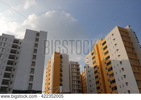 Low Angle View Of A Multi Storey Building Against The Blue Sky And Sunlight In The Background.