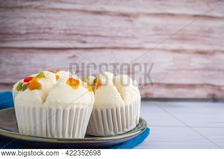 Side View Of Thai Steamed Cupcakes Or Thai Rice Flour Muffin Topped With Dry Fruit On Plate On Blue