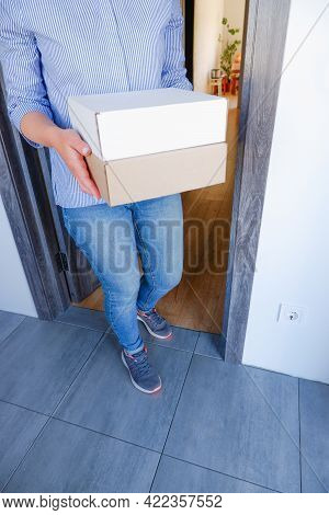 Delivery Of Parcels To The Door. A Woman Picks Up A Box With Goods Delivered By A Delivery Service F