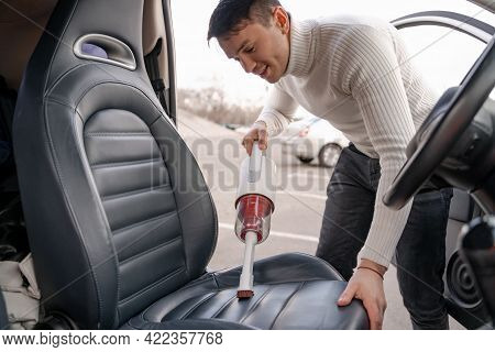 Man Vacuuming Car Seat With Vacuum Cleaner In Auto