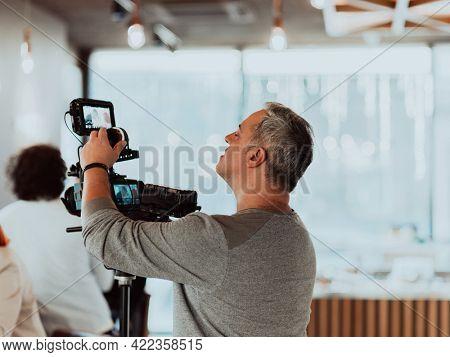 Cameraman working on professional camera taking stock footage