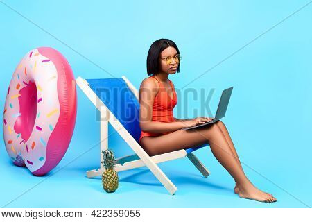 Online Work During Summer Vacation. Unhappy Black Lady Sitting In Lounge Chair With Laptop, Having T