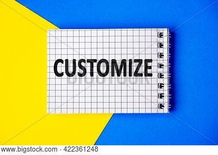 Text Customize On Page Notebook With Cage Lies On A Blue And Yellow Background, Top View.