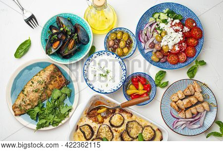 Assorted Greek Dishes On White Stone Background From Above, Moussaka, Grilled Fish, Souvlaki, Greek