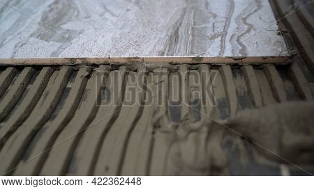 The Process Of Laying Ceramic Floor Tiles. Spreading Wet Mortar Before Applying Tiles. Applying Tile