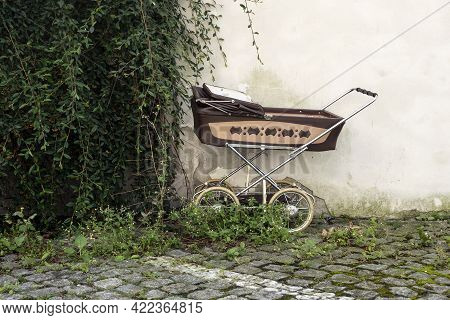 Old Baby-carriage From Commusim Era Left Near The Old Building Overgworn By Bush. The Junk On The St