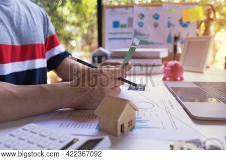 Professional Young Entrepreneur Open Saving Passbook With A Piggy Bank, Model House, Calculator, Inc