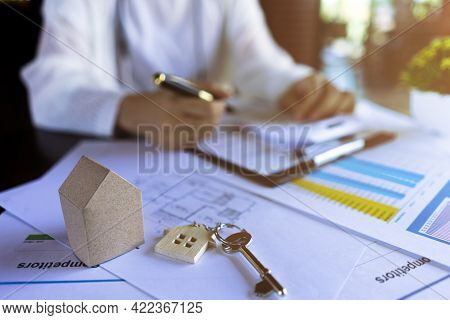 Professional Real Estate Agents Calculate The Price Of Housing With A House Keys, Miniature Model Ho