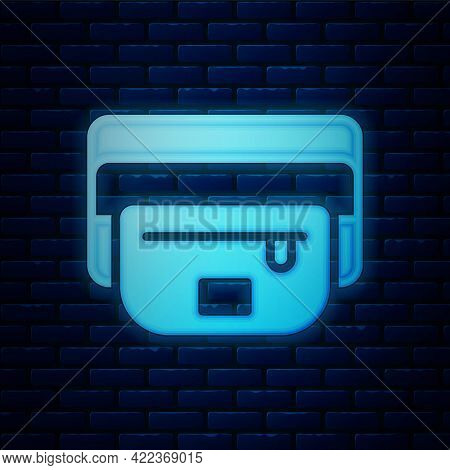 Glowing Neon Waist Bag Of Banana Icon Isolated On Brick Wall Background. Vector