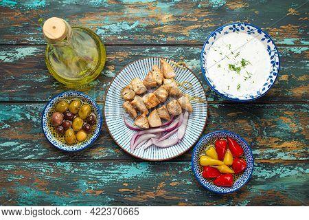 Greek Meat Souvlaki On Plate On Rustic Wooden Background From Above, Served With Olive Oil In Bottle