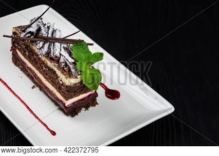 Plate with piece of delicious chocolate cake decorated with mint leaves on black wooden background