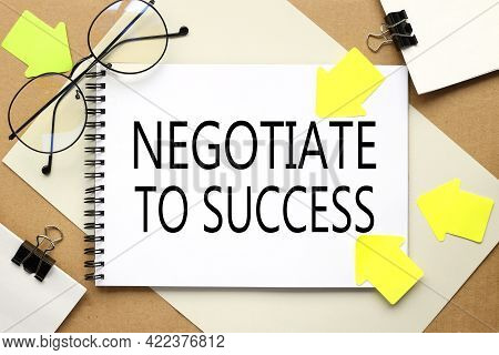 Negotiate To Success. Inscription On A Notebook On A Craft And Gray Background