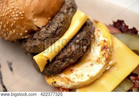 Two Servings Of Grilled Meats, Double Cheese And Scrambled Eggs In Hearty Cheeseburger. Double Meat