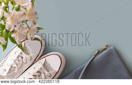 White Sneakers And A Blue Women's Bag. Trendy Handbag And Sport Shoes. Flat Lay.