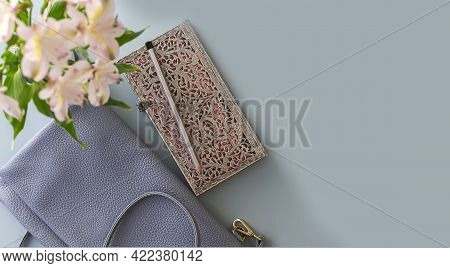Flat Lay Of Blue Working Table Background With Planner, Pencil , Elegant Female Cross Body Bag And P