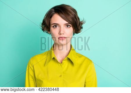 Photo Portrait Of Serious Woman In Green Shirt With Bob Hairstyle Isolated On Bright Teal Color Back