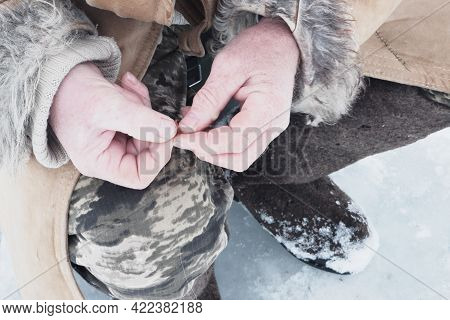 A Fisherman Puts Bait On A Fishing Hook In Winter.