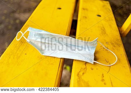 A Used Disposable Medical Mask Is Left On A Bench. End Of Quarantine. The End Of The Coronavirus Epi