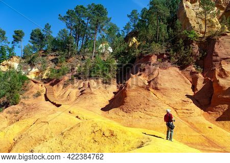 Photographer with a photo bag preparing for a photo shoot. Picturesque rocks from natural ocher. Travel to fabulous sunny Provence. Walk on the wooden deck for tourists. France