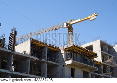 Construction Site. Facade Structure Of A Building Under Construction. Yellow Construction Crane Behi