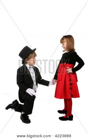 Young Boy Kneeling Down And Holding Girl'S Hand