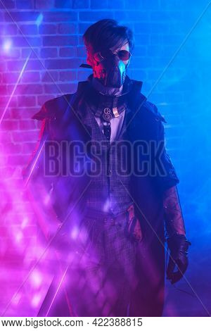 World of steampunk. Portrait of a courageous dieselpunk man on a smoky brickwall background.