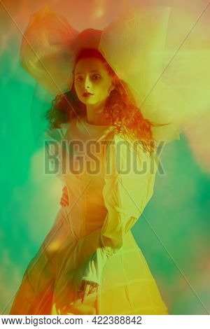 Fashion art. Portrait of a sophisticated fashion model girl with lush red curly hair posing in a white haute couture dress and a huge bow. Studio portrait in mixed colored light.