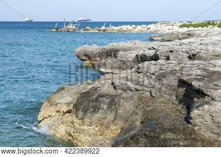 The Eroded Rocky Shore On Grand Bahama Island And Cargo Ships In A Background.