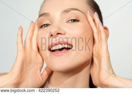 Female Beauty. Skin Rejuvenation. Aesthetic Cosmetology. Smiling Woman With Nude Makeup Touching Per