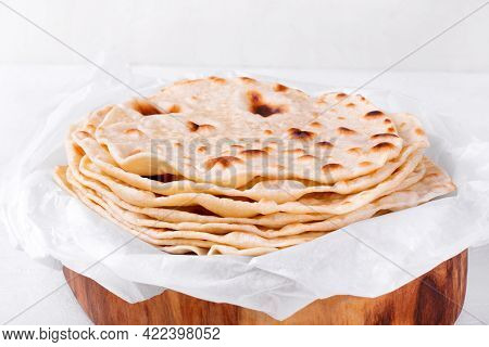 Stack Of Tortillas On Parchment Paper On White Table. Mexican Flatbread