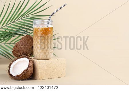 Still Life Iced Americano With Coconut Milk In A Highball And A Metal Tube On A Stone, Beige Backgro