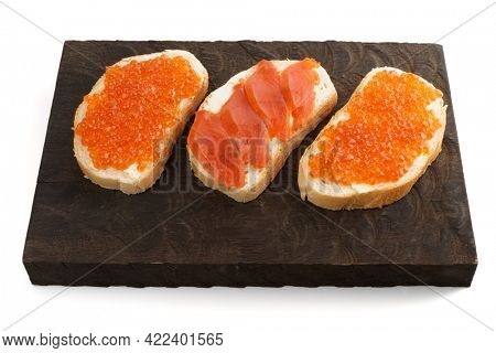 Open-face sandwiches with salmon roe and fillet on wooden board