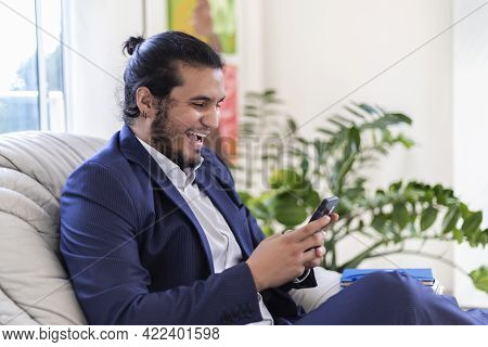 Young Latino Man With Long Hair And Piercings Dressed In Suit Smiling While Texting On Smart Phone I