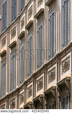 Long row of vintage rainessance windows shutter blinds at old house in medieval Trastevere district of Rome, Italy