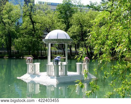 Romantic White Floating Gazebo House With Flowers For Swans On The Pond.