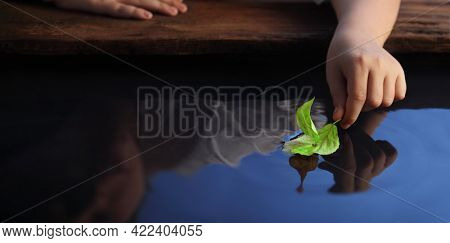 Boy in park play with boat in river. Green leaf-ship in children hand in water.