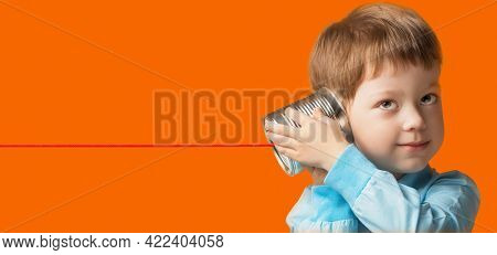 Boy Playing with Tin Can Phone. Isolate on orange background