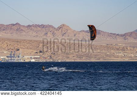 Eilat, Israel - May 24th, 2021: A Man Kite Surfing Off The Shore Of Eilat, Israel, With The Jordania