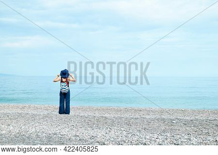 View From The Back Of Yong Woman With Backpack And Hat Looking At The Sea On The Pabble Beach.