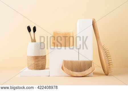 Natural Cosmetics In Beige Tones. Handmade Soap, Wooden Brushes And Bamboo Toothbrushes On White Pod