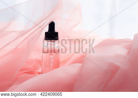 Hyaluronic Acid Bottle On Coral Fabric . Beauty Container. Skin Care. Vitamins For The Skin. Rejuven