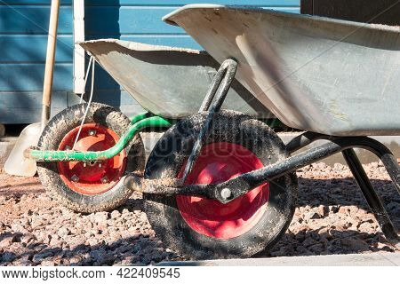 Two Dirty Wheelbarrows With Silver Bodies And Red Wheels Sit On The Gravel Driveway. A Building Wall