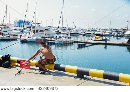 Sochi, Russia, July 27, 2019: Young Fisherman Man Fishing With A Rod On The Pier Sochi. Summer Time