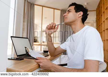 Pensive young hispanic man working studying on laptop computer while sitting at the desk at home