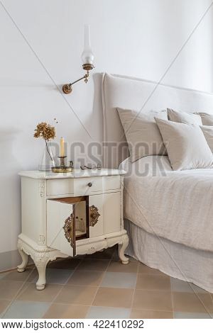 Interior Of Cozy House In Retro Style. Classic Bedroom With Candle, Glasses And Flowers On Wooden Be