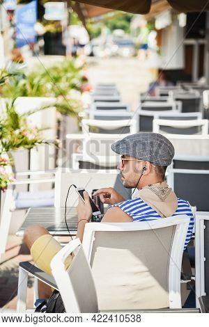 Sochi, Russia, July 27, 2019: Traveler Man Sits With His Back In A Cafe On The Pier, Listens To Musi
