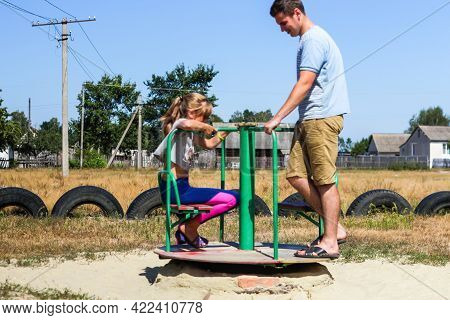 Defocus Emotion Expression Preteen Girl Riding A Carousel On Playground With Young Brunette Man, Guy