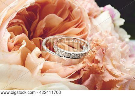 Pair Of Platinum Wedding Rings. Closeup Of White Golden Wedding Rings On Floral Background. Bride Ri