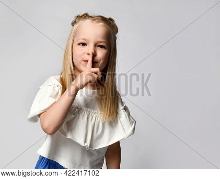 Childrens Secret. Close Up Portrait Of A Little Blonde Girl Showing A Gesture Of Silence On A White