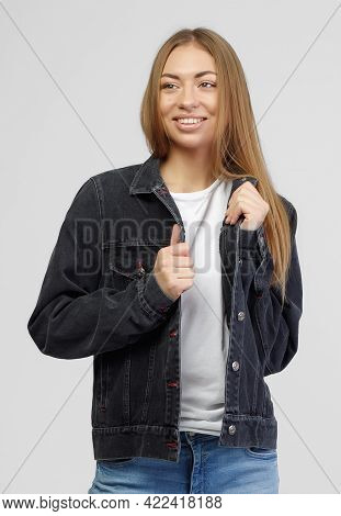 Girl In A Denim Black Jacket And Blue Denim Pants On A White Background.
